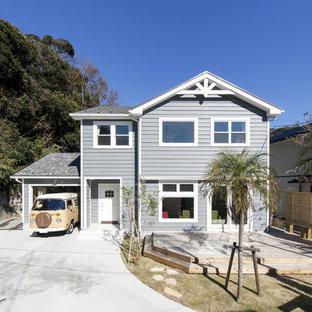 Ejemplo de fachada de casa azul, marinera, de dos plantas, con revestimientos combinados y tejado de teja de barro