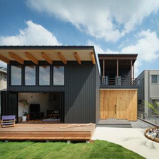 他の地域のビーチスタイルのおしゃれな二階建ての家 (メタルサイディング、黒い外壁、片流れ屋根、戸建、金属屋根) の写真