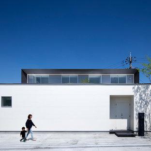 Imagen de fachada de casa blanca, minimalista, de tamaño medio, de dos plantas, con revestimientos combinados, tejado a dos aguas y tejado de metal