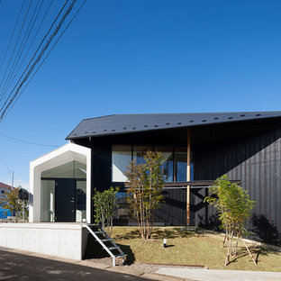 他の地域のアジアンスタイルのおしゃれな陸屋根の家 (マルチカラーの外壁) の写真