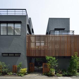 Imagen de fachada gris, minimalista, de dos plantas, con revestimiento de hormigón y tejado plano