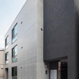 Modelo de fachada de piso negra, minimalista, grande, de tres plantas, con tejado plano y revestimiento de hormigón