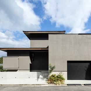 Immagine della facciata di una casa unifamiliare grigia etnica a due piani con tetto piano