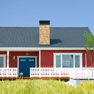 Large scandinavian red one-story wood exterior home idea in Other with a clipped gable roof