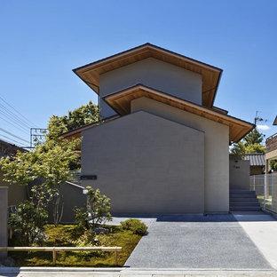 Ejemplo de fachada beige, asiática, con tejado a dos aguas
