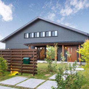 Ejemplo de fachada de casa negra, asiática, de dos plantas, con tejado a dos aguas y tejado de metal