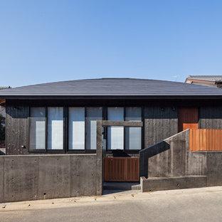 Modelo de fachada negra, asiática, con revestimiento de madera y tejado a doble faldón