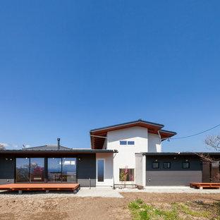他の地域のコンテンポラリースタイルのおしゃれな切妻屋根の家 (グレーの外壁) の写真