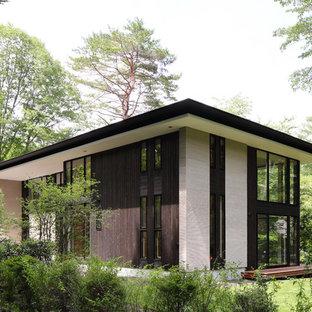 他の地域のモダンスタイルのおしゃれな家の外観 (木材サイディング、黒い外壁、寄棟屋根、戸建、金属屋根) の写真
