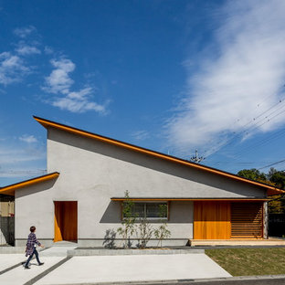Inspiration for a zen gray house exterior remodel in Other with a shed roof