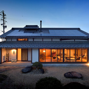 Esempio della facciata di una casa unifamiliare bianca etnica a due piani con tetto a capanna e copertura in tegole
