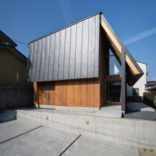 Imagen de fachada de casa asiática, a niveles, con revestimiento de madera y tejado de metal