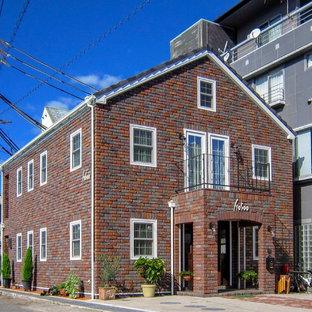Foto de fachada de casa beige, urbana, de tamaño medio, de dos plantas, con revestimiento de ladrillo, tejado a dos aguas y tejado de teja de barro