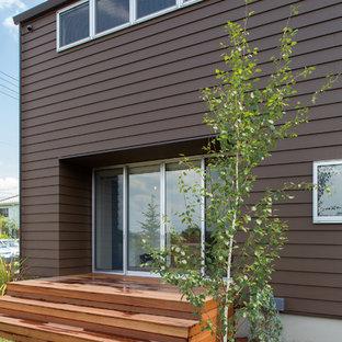 Imagen de fachada de casa marrón, urbana, a niveles, con tejado a dos aguas y tejado de metal