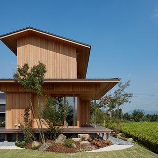 他の地域のアジアンスタイルのおしゃれな切妻屋根の家 (木材サイディング、茶色い外壁) の写真