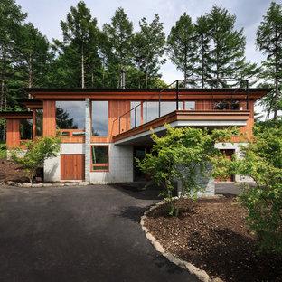 他の地域のコンテンポラリースタイルのおしゃれな家の外観 (茶色い外壁、陸屋根) の写真