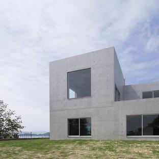Modelo de fachada gris, minimalista, con revestimiento de hormigón y tejado plano