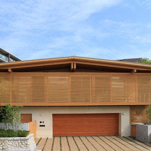 Idée de décoration pour une façade de maison marron asiatique à un étage avec un revêtement mixte et un toit à deux pans.