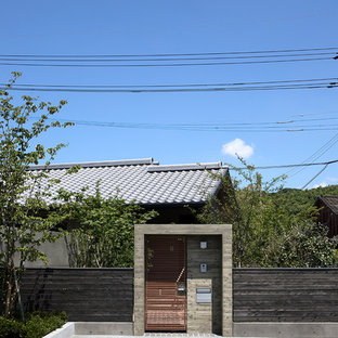 Diseño de fachada de casa gris, asiática, pequeña, de una planta, con revestimiento de aglomerado de cemento, tejado a dos aguas y tejado de teja de barro
