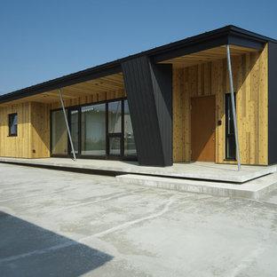 他の地域のアジアンスタイルのおしゃれな陸屋根の家 (黒い外壁) の写真