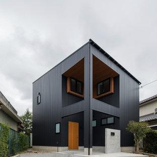 他の地域のミッドセンチュリースタイルのおしゃれな家の外観 (黒い外壁) の写真
