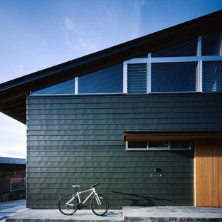 他の地域のアジアンスタイルのおしゃれな陸屋根の家 (緑の外壁) の写真