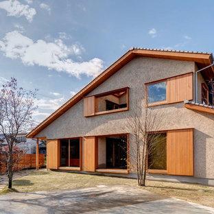 Zen beige two-story gable roof idea in Osaka