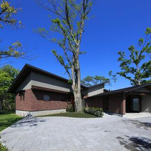 他の地域のモダンスタイルのおしゃれな家の外観 (レンガサイディング、茶色い外壁) の写真