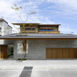 Design ideas for an asian two-storey brick grey exterior in Other with a flat roof.