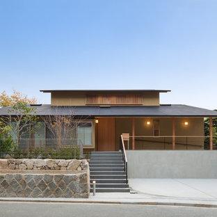 Foto de fachada marrón, asiática, de dos plantas, con tejado a dos aguas