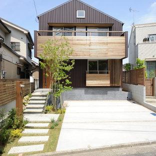 Foto på ett minimalistiskt brunt hus, med två våningar, sadeltak och tak i metall