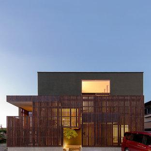 Ispirazione per la facciata di una casa unifamiliare grigia etnica a due piani con rivestimenti misti e tetto piano