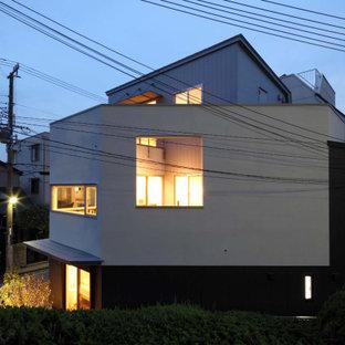 Diseño de fachada blanca, moderna, pequeña, de tres plantas, con revestimiento de estuco, tejado a doble faldón y tejado de metal