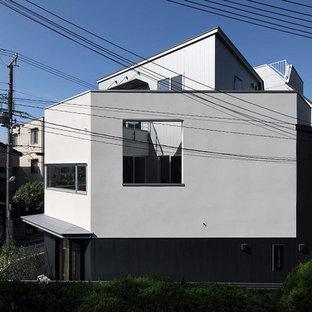 Modelo de fachada blanca, moderna, pequeña, de tres plantas, con revestimiento de estuco, tejado a doble faldón y tejado de metal