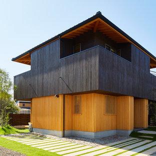 他の地域のアジアンスタイルのおしゃれな家の外観 (木材サイディング、マルチカラーの外壁) の写真