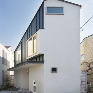 東京都下のコンテンポラリースタイルのおしゃれな家の外観 (漆喰サイディング、半切妻屋根) の写真