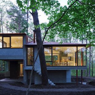 Imagen de fachada de casa gris, minimalista, grande, a niveles, con revestimiento de hormigón, tejado a doble faldón y tejado de metal