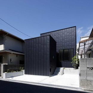 他の地域の中くらいのラスティックスタイルのおしゃれな家の外観 (メタルサイディング、黒い外壁) の写真