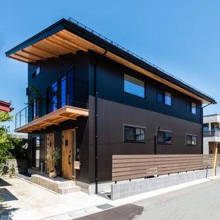 Diseño de fachada de casa negra, de estilo zen, grande, de dos plantas, con revestimientos combinados, tejado de un solo tendido y tejado de metal