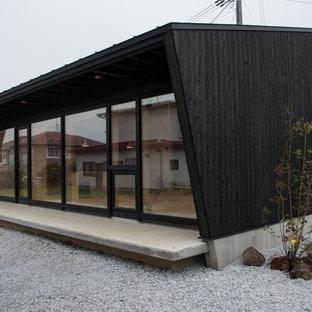 他の地域のアジアンスタイルの家の外観の画像 (木材サイディング、黒い外壁、片流れ屋根)