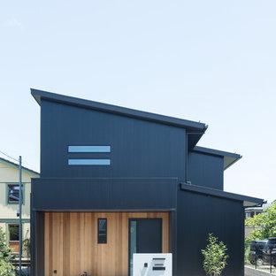 他の地域のコンテンポラリースタイルのおしゃれな二階建ての家 (黒い外壁、片流れ屋根、混合材サイディング、戸建) の写真