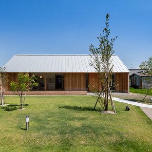 Inspiration för ett orientaliskt brunt trähus, med allt i ett plan och sadeltak
