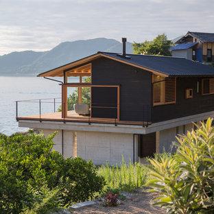 Imagen de fachada de casa negra, ecléctica, de dos plantas, con tejado a dos aguas y tejado de metal