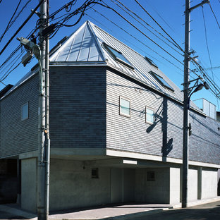 Example of a small minimalist pink three-story brick house exterior design in Tokyo with a shed roof and a metal roof