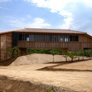 他の地域の巨大なアジアンスタイルのおしゃれな家の外観 (木材サイディング) の写真