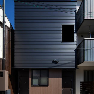 Modelo de fachada de piso negra, moderna, pequeña, de tres plantas, con revestimiento de metal, tejado de un solo tendido y tejado de metal