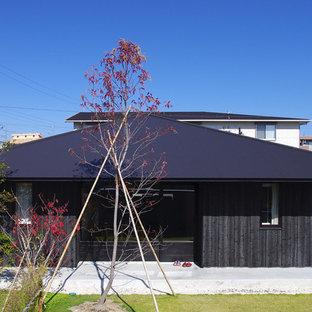 Foto de fachada negra, asiática, pequeña, de una planta, con revestimiento de madera y tejado a cuatro aguas