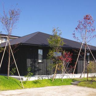 Ejemplo de fachada negra, de estilo zen, pequeña, de una planta, con revestimiento de madera y tejado a cuatro aguas