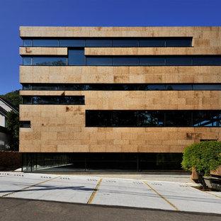 Imagen de fachada marrón, moderna, de tres plantas, con tejado plano