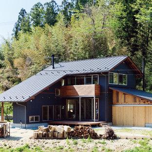 他の地域のアジアンスタイルのおしゃれな二階建ての家 (黒い外壁、切妻屋根) の写真